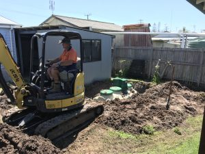 Compact home sewage treatment plant being installed in small backyard at Sandon River