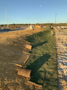 The turf is rolled out over the effluent disposal area which is now only visible as a grassy mound.